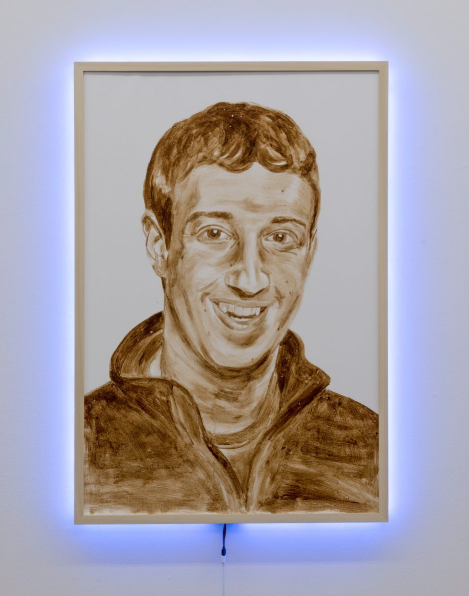 """shithead 1 (Mark Zuckerberg)"", 2014, human feces with LED light fame, 48 x 36 inches, 121.9 x 91.4 cm"
