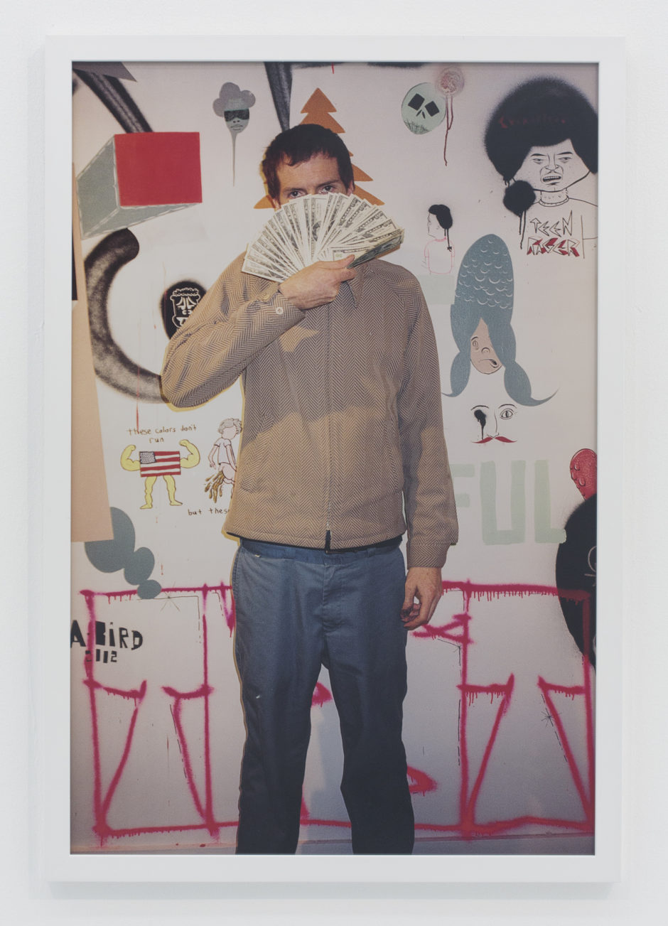 "Andrew Jeffrey Wright, ""Holding money in front of wall of me and Barry's art"", 2002, digital c-print, 36 x 24 inches"